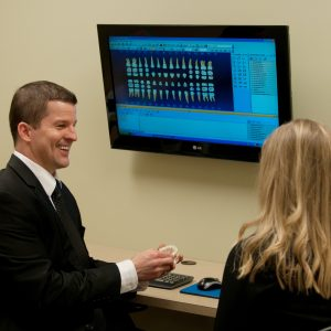 Image of Dr. Brad Alderman discussing a possible tooth extraction with a patient in Lincoln, NE.