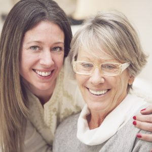 Image of a happy patient with her daughter, who found dentures to be a great solution for her dental needs.