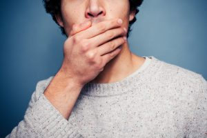 Image of a patient covering his mouth because he has dental problems associated with yeast infection in a mouth.