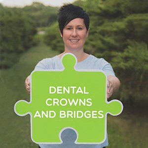 Image of a dental professional from Coddington Dental holding a dental crowns and bridges sign.