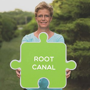 Image of a dental professional in Lincoln, NE, holding a root canal sign.