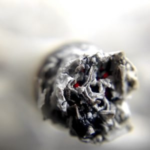 Image of a burning cigarette, which can also have adverse effects on or cause a yeast infection in a mouth.