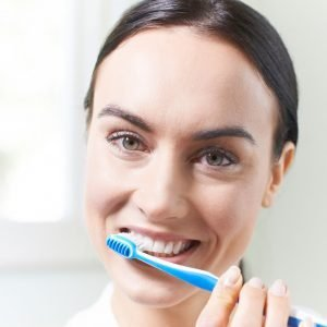 Image of a Coddington Dental patient brushing her teeth after being educated by her hygienist.